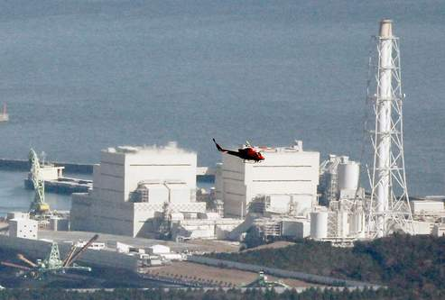 A helicopter flies past Japan's Fukushima Daiichi No.1 Nuclear reactor