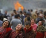 Family members break down during the cremation of earthquake victims in Bhaktapur near Kathmandu, Nepal, Sunday, April 26, 2015. A strong magnitude 7.8 earthquake shook Nepal's capital and the densely populated Kathmandu Valley before noon Saturday, causing extensive damage with toppled walls and collapsed buildings, officials said. (AP Photo/Niranjan Shrestha)
