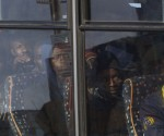 Rescued migrants sit on a bus after disembarking from an Italian Coast Guard ship in the harbor of Lampedusa, Southern Italy, Saturday, May 2, 2015. Ships from Italy and France rescued more than 1,400 migrants on Saturday after smugglers' boats ran into trouble in the Mediterranean Sea near Libya. (AP Photo/Mauro Buccarello)